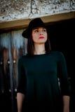 Muchacha morena en negro con un sombrero elegante y una puerta de madera vieja Fotografía de archivo