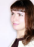 Muchacha morena en perfil que sonríe y que mira adelante Imágenes de archivo libres de regalías