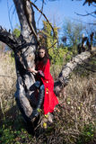 Muchacha morena en un impermeable rojo Foto de archivo