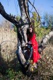 Muchacha morena en un impermeable rojo Imagen de archivo libre de regalías