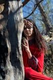 Muchacha morena en un impermeable rojo Imagen de archivo