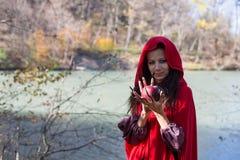 Muchacha morena en un impermeable rojo Fotos de archivo