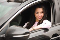 Muchacha morena feliz hermosa en la ventanilla del coche imagenes de archivo