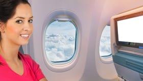 Muchacha morena feliz hermosa que se sienta en el aeroplano fotografía de archivo