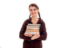 Muchacha morena feliz joven del estudiante en ropa marrón del deporte con las coletas y los libros en sus manos que sonríe en la  Fotografía de archivo libre de regalías