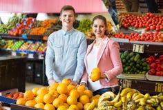 Muchacha morena feliz y frutas cítricas de compra sonrientes del novio Imagen de archivo