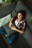 Muchacha morena fresca que se sienta en el sofá Imagen de archivo libre de regalías