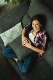 Muchacha morena fresca que se sienta en el sofá Fotografía de archivo