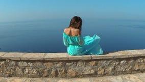 Muchacha morena hermosa con el pelo largo sano que se relaja en roca sobre la isla sobre el mar y el cielo azul Sveti Stefan almacen de metraje de vídeo
