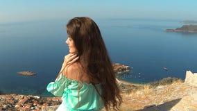 Muchacha morena hermosa con el pelo largo sano que se relaja en roca sobre la isla sobre el mar y el cielo azul Sveti Stefan metrajes