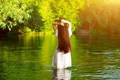Muchacha morena hermosa con el pelo oscuro muy largo y grueso que se coloca en el agua Fotografía de archivo libre de regalías