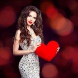 Muchacha morena hermosa con el regalo rojo del corazón para el día de tarjetas del día de San Valentín Imagen de archivo libre de regalías