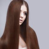 Muchacha morena hermosa con un pelo perfectamente liso y un maquillaje clásico Cara de la belleza fotos de archivo libres de regalías