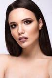 Muchacha morena hermosa con un pelo perfectamente liso y un maquillaje clásico Cara de la belleza foto de archivo