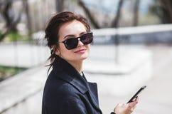 Muchacha morena hermosa elegante joven en las gafas de sol que miran la cámara que sostiene su smartphone en calle en primavera fotografía de archivo libre de regalías