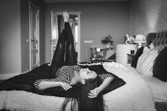 Muchacha morena hermosa en cama en la actitud atractiva, marco blanco y negro Imagenes de archivo