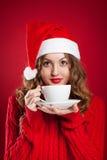 Muchacha morena hermosa en el sombrero de Papá Noel que sostiene la taza blanca Imagen de archivo