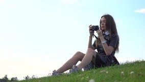 Muchacha morena hermosa en el vestido negro que se sienta en el césped y que hace las fotos con su cámara Fotografía aficionada 4 almacen de metraje de vídeo