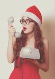 Muchacha morena hermosa en sombrero de la Navidad con el teléfono en yello Fotografía de archivo libre de regalías