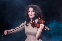 Muchacha morena hermosa en un vestido beige ligero que toca el violín Concepto para las noticias de la música Fondo ahumado Fotografía de archivo libre de regalías