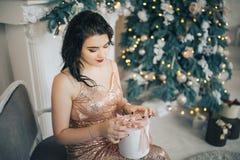 Muchacha morena hermosa en un vestido largo que se sienta en un cuarto cerca de un árbol de navidad Imagen de archivo libre de regalías