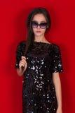 Muchacha morena hermosa en un vestido negro y gafas de sol Morenita con el pelo negro largo fotografía de archivo libre de regalías