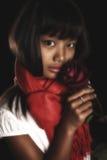 Muchacha morena hermosa en una bufanda roja alrededor de su cuello, con una rosa roja en su mano Fotografía de archivo