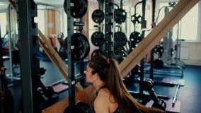 Muchacha morena hermosa joven con el pelo largo en el gimnasio que hace ejercicios en la posición en cuclillas con una barra 4 K almacen de video