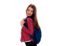 Muchacha morena hermosa joven del estudiante con la mochila en su sonrisa de los hombros aislada en el fondo blanco Imagenes de archivo