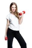Muchacha morena hermosa joven que lleva a cabo pesas de gimnasia Fotos de archivo libres de regalías