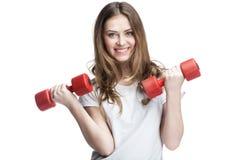 Muchacha morena hermosa joven que lleva a cabo pesas de gimnasia Fotos de archivo