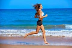 Muchacha morena hermosa que corre en una playa del verano Imagenes de archivo