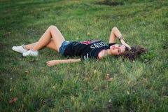 Muchacha morena hermosa que descansa sobre hierba del césped Una muchacha adolescente brillante joven ama deportes moda de la cal Foto de archivo libre de regalías