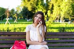 Muchacha morena hermosa que habla en el teléfono en un banco que se sienta del parque en vestido, mujer de negocios del día de ve fotos de archivo