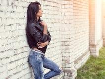 Muchacha morena hermosa que se coloca en la pared de ladrillo blanca Ella sueña Fotografía de archivo