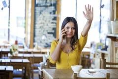 Muchacha morena hermosa que se sienta en una cafetería Fotografía de archivo