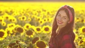Muchacha morena hermosa que sonríe en campo del girasol almacen de video