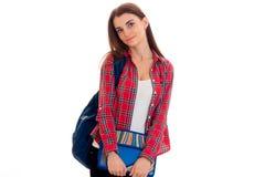 Muchacha morena joven adorable del estudiante con la mochila azul aislada en el fondo blanco Imágenes de archivo libres de regalías