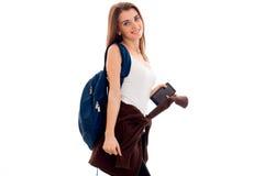 Muchacha morena joven del estudiante con el backpackand azul y teléfono móvil en sus manos que presentan y que miran la cámara Imagen de archivo libre de regalías