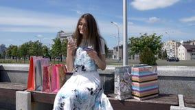 Muchacha morena joven feliz con el pelo largo que se sienta en un banco usando un teléfono elegante y tarjetas del kcredit al air fotos de archivo libres de regalías