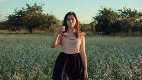 Muchacha morena joven hermosa en falda negra que camina en el campo presentación delante de la cámara y tacto del pelo almacen de metraje de vídeo
