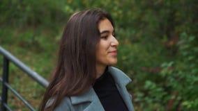 Muchacha morena joven hermosa que camina en el parque en otoño almacen de metraje de vídeo