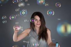 Muchacha morena joven que infla burbujas de jabón en el backgroun gris Fotos de archivo