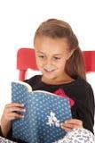 Muchacha morena joven que mira la lectura emocionada un libro Fotografía de archivo libre de regalías