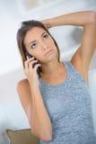 Muchacha morena joven que se sienta en el sofá con el teléfono Fotos de archivo