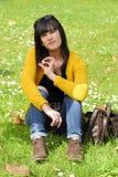 Muchacha morena joven que se sienta en hierba en parque, al aire libre Imágenes de archivo libres de regalías