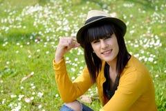 Muchacha morena joven que se sienta en hierba en parque, al aire libre Foto de archivo