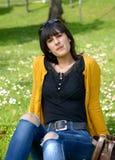 Muchacha morena joven que se sienta en hierba en parque, al aire libre Fotografía de archivo libre de regalías