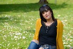 Muchacha morena joven que se sienta en hierba en parque, al aire libre Imagenes de archivo