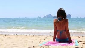 muchacha morena joven que se sienta en la playa metrajes